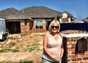 Cherie Pope outside her new home in Moore.