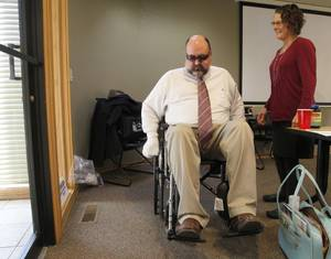 Oklahoman reporter Richard Mize maneuvers a wheelchair during OSHBA's Aging in Place certification training class. PHOTO BY PAUL HELLSTERN/THE OKLAHOMAN